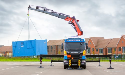 Lorry loader lifting 24ft unit in carpark